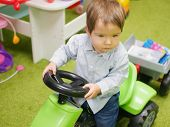 The Child Is Riding A Toy Car. A Child Plays With Toys At Home. Little Child Plays With Toys In Kind poster