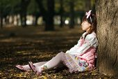 stock photo of lolita  - sad japanese lolita leaning against tree in park - JPG