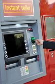 picture of automatic teller machine  - Female hand inserting a bank card at an automatic bank teller machine - JPG