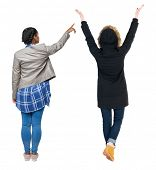 Back view of two pointing young girl in winter jacket. Rear view people collection. backside view of poster