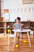 Beautiful toddler boy drawing cute draw using colored pencils at kindergarten poster