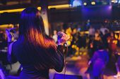 Beautiful Singing Girl. Beauty Glamor Fashion Woman With Microphone Over Blinking Bokeh Night Backgr poster
