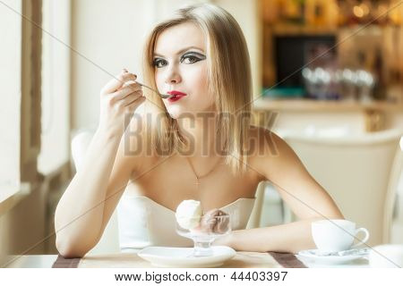 A beautiful woman in the restaurant is eating ice cream
