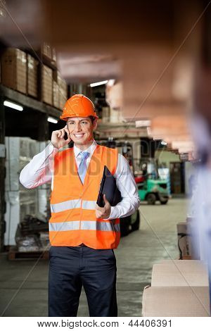 Young male supervisor in orange protective vest using cell phone at warehouse
