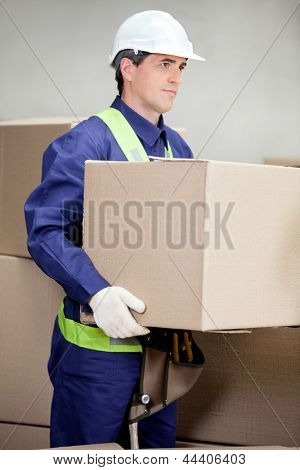 Portrait of foreman lifting cardboard box at warehouse