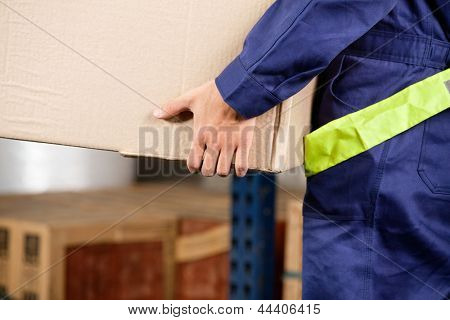 Midsection of young foreman in uniform carrying cardboard box in warehouse