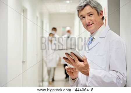 Portrait of mature male doctor holding digital tablet with colleagues walking in background