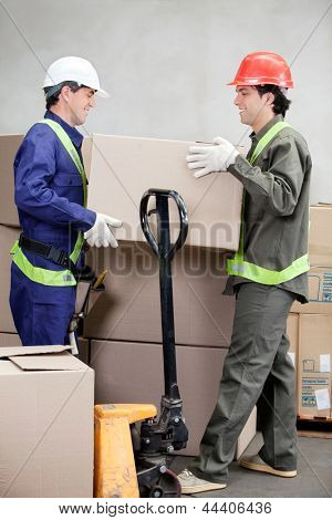 Two foremen lifting cardboard box at warehouse