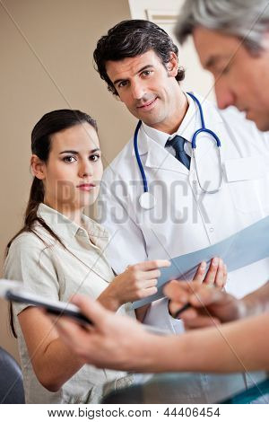 Portrait of multiethnic medical coworkers standing together with man in foreground