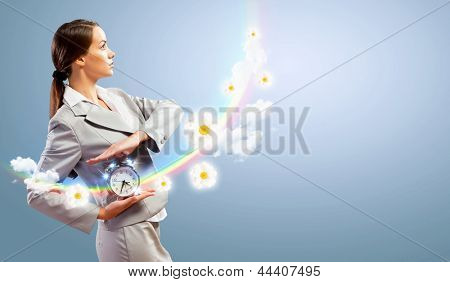 Image of young businesswoman holding alarmclock against illustration background