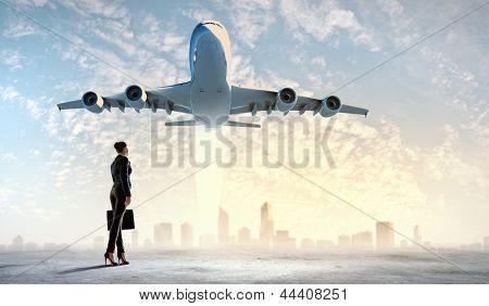 Imagem de mulher de negócios segurando mala olhando avião no céu