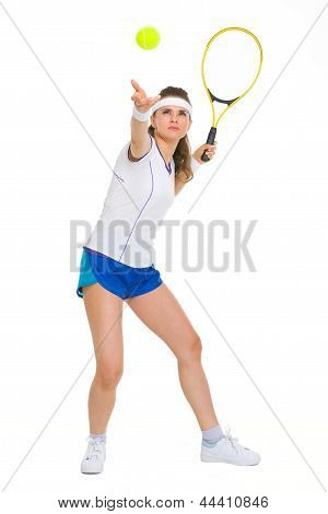 Full Length Portrait Of Female Tennis Player Serving Ball