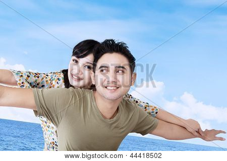 Asian Couple Pretend To Fly Over Blue Sky