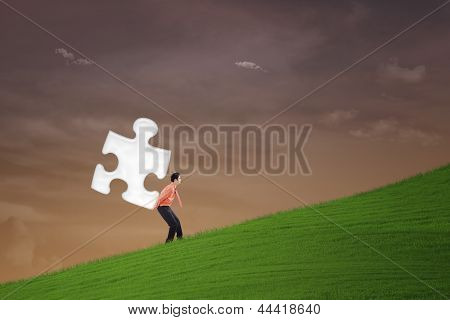 Businessman Carry Puzzle On Steep Hill
