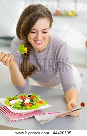 Happy Young Housewife Eating Fresh Salad And Reading Magazine In