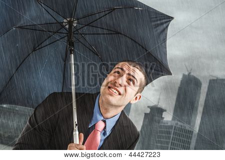 Businessman under heavy rain