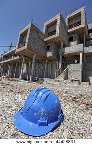 broken hard hat and unfinished apartments in background - crisis in development industry