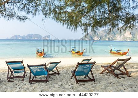 Bamboo beach chairs and traditional long-tail boats on beautiful bay of Koh Phi Phi Island Thailand