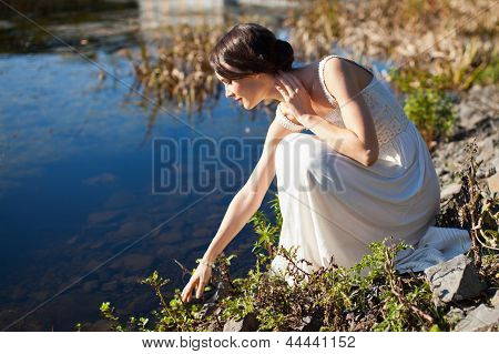 Young Woman Sitting By Water