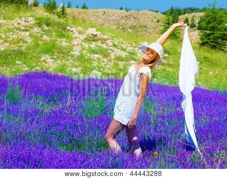 Attractive young lady wearing summer hat and dance with white shawl on floral field, fresh purple lavender flowers, relaxation outdoors