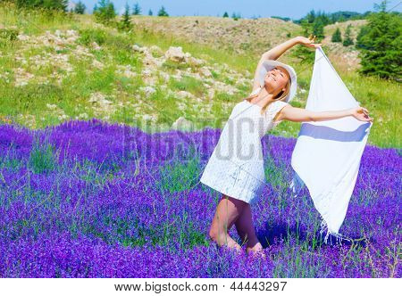 Beautiful blond woman holding in hands white shawl and dancing in purple lavender flower field, sunny day, summer season, pleasure concept