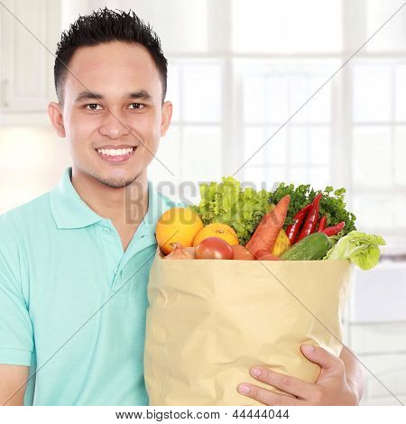 Man Holding Shopping Bag Full Of Groceries