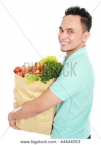 Man With Paper Bag Full Of Fruits And Vegetables