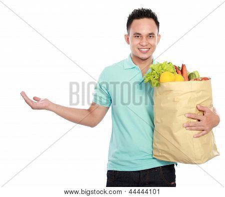 Man Holding Shopping Bag Full Of Groceries Presenting