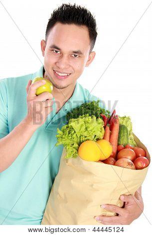 Man Holding Shopping Bag Full Of Groceries