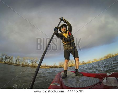 mature male paddler enjoying workout on stand up paddleboard (SUB), calm lake in Colorado, early spring