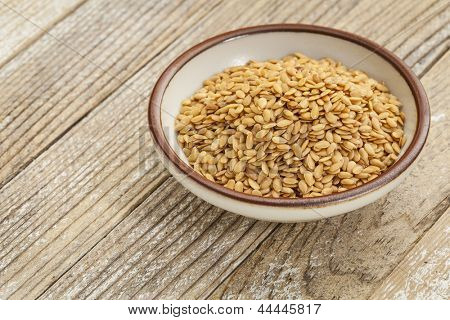 gold flux seeds in a small ceramic bowl against a grunge wood surface
