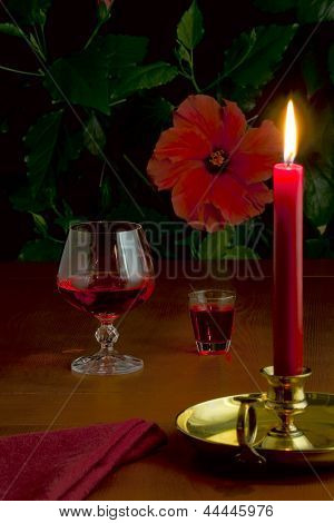 A Glass Of Red Wine, A Small Glass With Liquor And A Burning Candle In A Candlestick