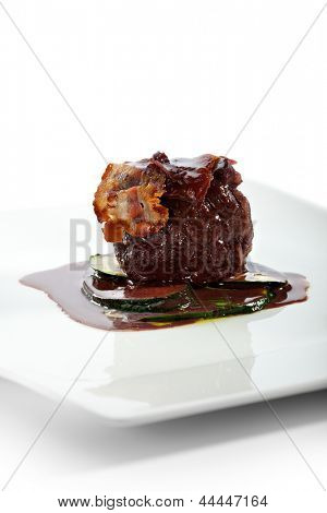Fillet of Beef with Zucchini and Wine Sauce. Topped with Bacon