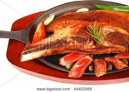 fresh roasted lamb meat fillet ready on metal iron pan with tomatoes, green pepper , and garlic isolated on white background