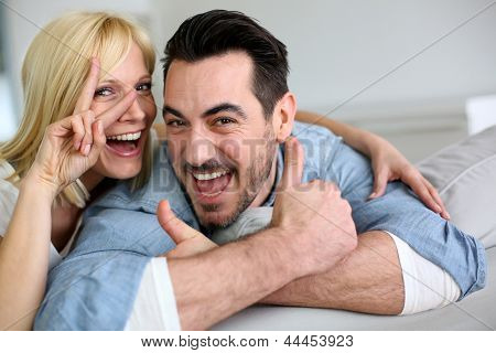 Cheerful couple showing thumbs up to camera