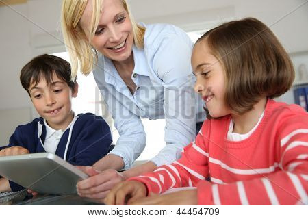 Teacher in class with kids using electronic tablet