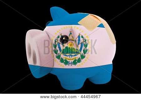 Bankrupt Piggy Rich Bank In Colors Of National Flag Of El Salvador    Closed With Bandage