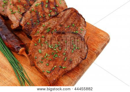 fresh roasted red meat with thyme and chives on wooden plate isolated on white background
