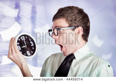 Stressed Male Office Worker Holding Overtime Clock