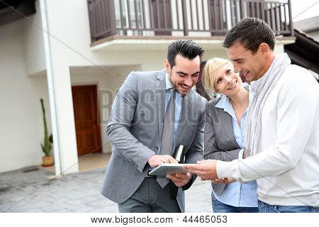 Real-estate-agent showing house plan on digital tablet