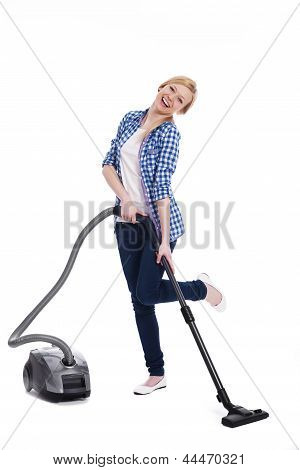 Pretty and smiling woman vacuuming a floor