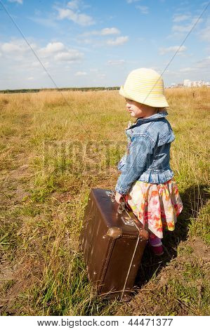 lonely girl with suitcase. Back view