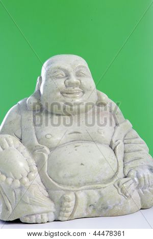 A Buddha Figurine Against A Green Background