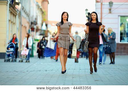 Duas mulheres elegantes andando a cidade lotada com sacos de compras