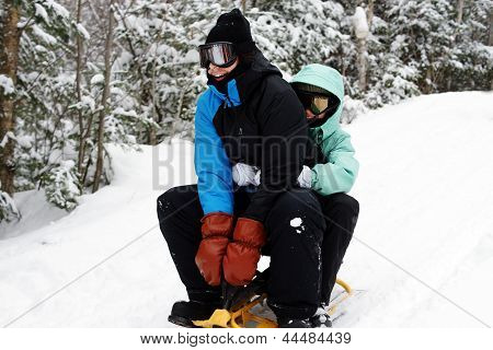 Young Couple Sliding During Winter