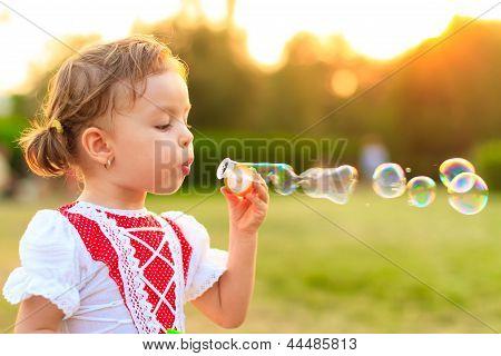 Child Blowing Soap Bubbles.