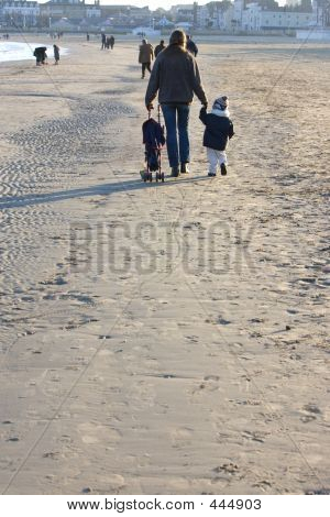 Young Woman And Toddler Son On Beach In Winter