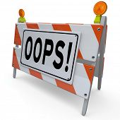 picture of oops  - The word Oops on a construction barricade to warn of a mistake or error causing a problem - JPG