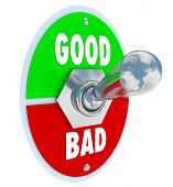 foto of good-vs-evil  - The words Good and Evil on a toggle switch lever to decide or judge whether something is beneficial or harmful to you in life - JPG