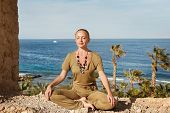 stock photo of padmasana  - Young woman meditating in yoga asana near sea - JPG